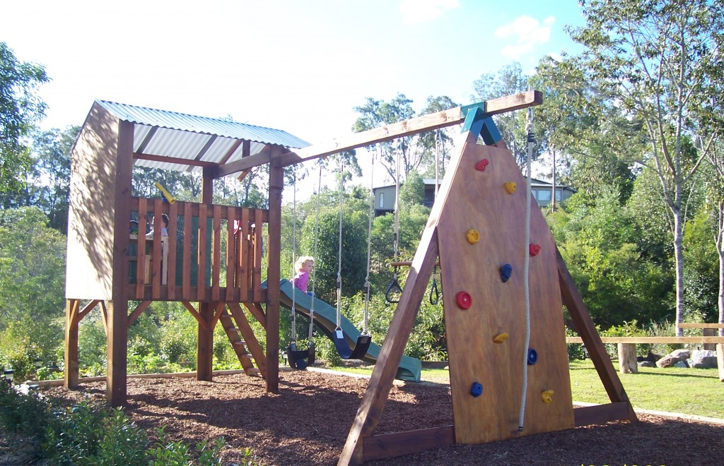 Swing set connected to a cubby house